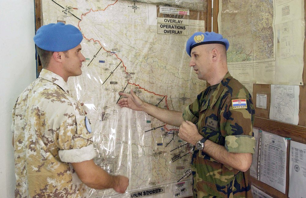 Two peacekeepers of the United Nations Military Observer Group in India and Pakistan (UNMOGIP) review their plans for the day at Bhimbar UN Field Station, Pakistan. Their mandate is to be a neutral party in the India and Pakistan situation. (20 October, 2005, Bhimbar, Pakistan)