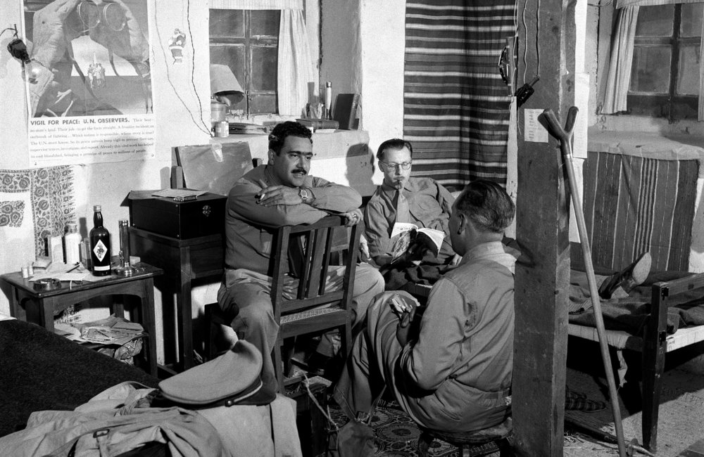The members of a field team of the UN Military Observer Group in India and Pakistan spending a quiet evening in their living quarters at the Tangdhar station. At this station, the military observers and UN radio operator are quartered in a mud hut which they share with the headquarters of an Indian battalion.   The members of the UN team are: Major Emilio Altieri (back to camera), of Uruguay; Major Pierre Jooris (reading), of Belgium; and radio operator Guillermo Encastilla. (01 January, 1955, Kashmir)