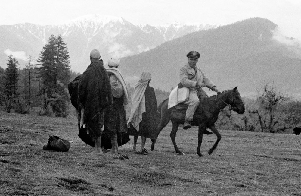 The members of the U.N. Military Observer Group in India and Pakistan- Major Emilio Altieri (Uruguay) - riding a horse while on patrol along the cease-fire line; here, he exchanges a few words with a group of Kashmiris he met on the way. (01 January, 1955, Kashmir)