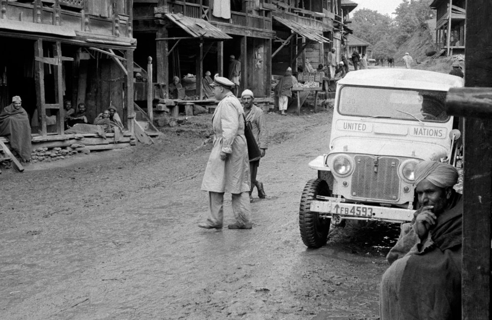 A member of the U.N. Military-Observer Group in India and Pakistan- Major Emilio Altieri (Uruguay)- on his way to a field station on the Kashmir cease-fire line, stops his jeep in front of the bazaar in a village to interview the inhabitants. (01 January, 1955, Kashmir)