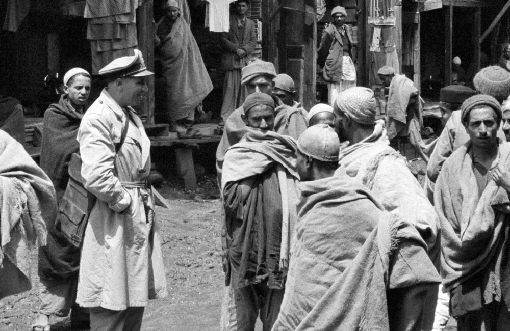 Major Emiliio Altieri (Uruguay), one of the members of the U.N. Military observer Group in India and Pakistan, talks with the inhabitants of a small mountain village in Kashmir. Seen in the background are the shops of the bazaar. (01 January, 1955, Kashmir)